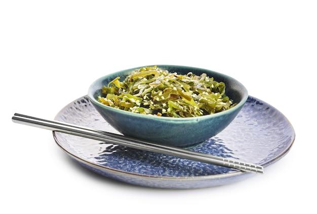 Чаша с вкусными водорослями и палочками для еды на белом