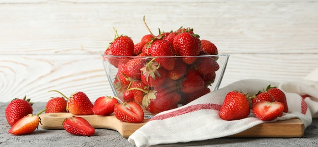 Bowl with tasty strawberry on gray table. summer berry