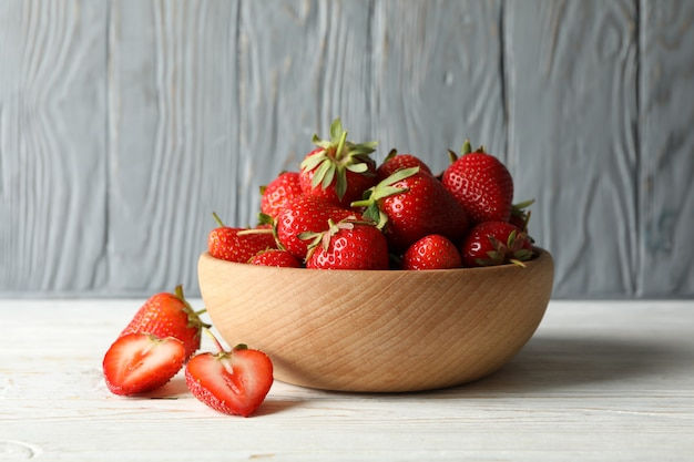Bowl with tasty strawberry on wooden table