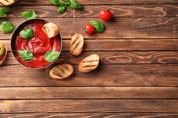 木製のテーブルの上においしいトマトソースと焼きたてのパンとボウル