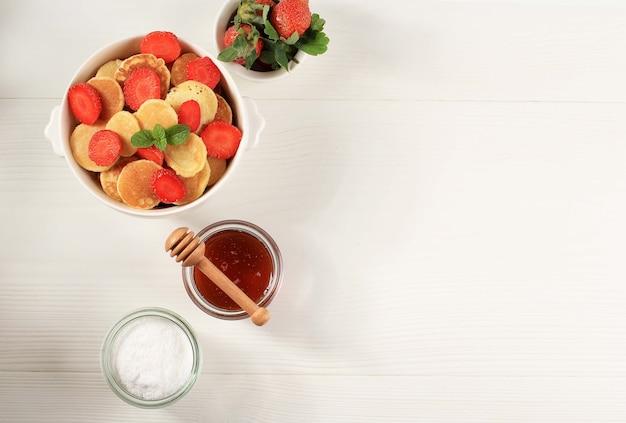 白い背景の上のイチゴとミントの葉と小さなパンケーキシリアルとボウル。と木のプレート。トレンディな料理。ミニシリアルパンケーキ。景観オリエンテーション