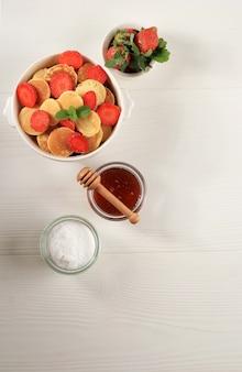 白い背景の上のイチゴとミントの葉と小さなパンケーキシリアルとボウル。と木のプレート。トレンディな料理。ミニシリアルパンケーキ。縦向き