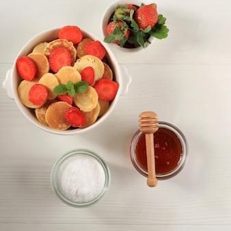 白い木製の背景にイチゴとミントの葉と小さなパンケーキシリアルとボウル。トレンディな料理。ミニシリアルパンケーキ。正方形の画像、上面図