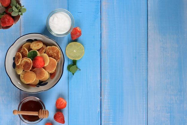 青い背景にイチゴ、レモン、ミントの葉と小さなパンケーキシリアルとボウル。トレンディな料理。ミニシリアルパンケーキ。景観オリエンテーション