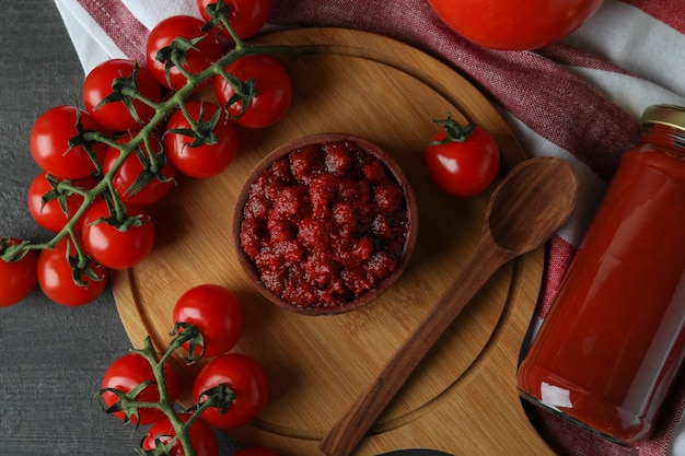 材料が入った暗い木製のテーブルにトマトペーストを入れたボウル