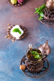 Bowl with turkish cotton candy pismaniye and black tea with mint on a dark surface