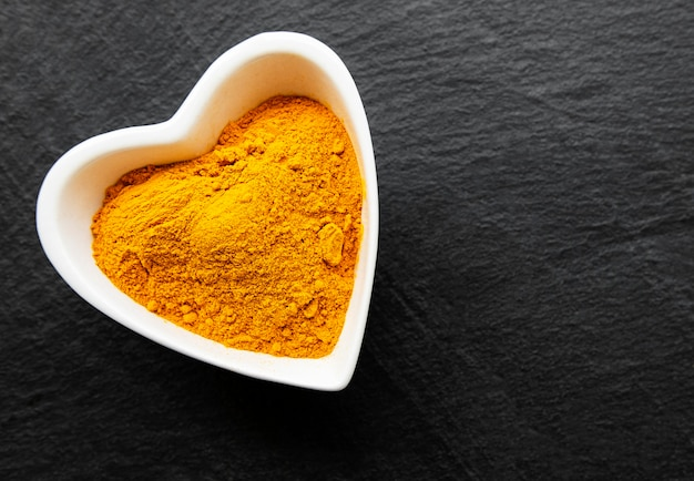 Bowl with turmeric powder  on a black concrete background