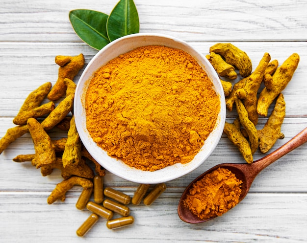 Bowl with turmeric powder and dry roots on a wooden background