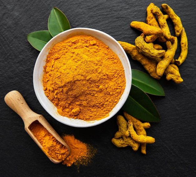 Bowl with turmeric powder and dry roots