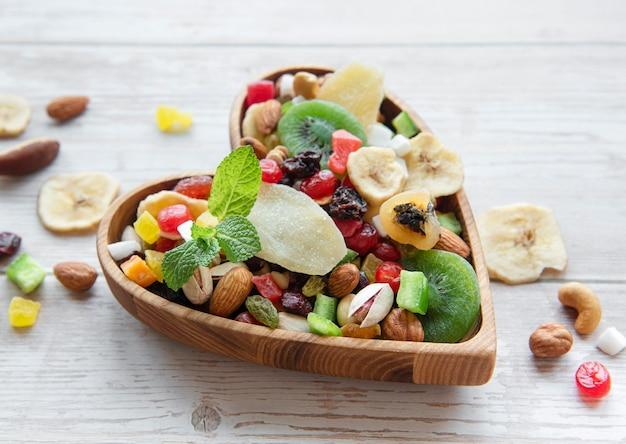 다양 한 말린 과일과 견과류 나무 표면에 그릇