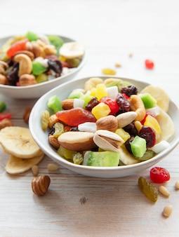 나무 표면에 다양한 말린 과일과 견과류와 그릇
