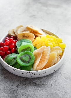 Bowl with various dried fruits  on a gray concrete surface