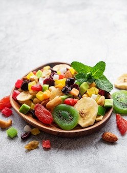 Bowl with various dried fruits and nuts on a gray concrete surface