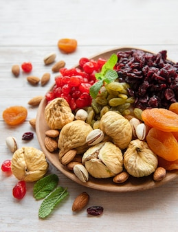 Bowl with various dried fruits and nuts on a wooden  surface