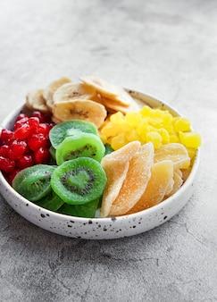 회색 콘크리트 표면에 다양한 말린 과일 그릇