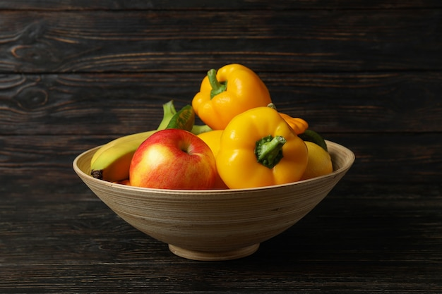 Чаша с овощами и фруктами на деревянных фоне