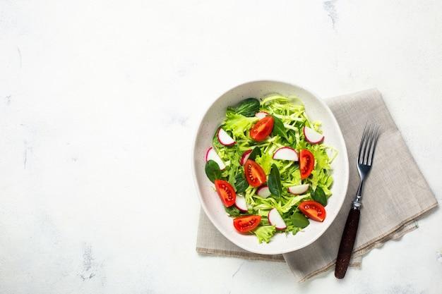 ベジタリアンの新鮮なサラダを入れたボウル。健康食品、ダイエットランチ。白い背景の上面図。
