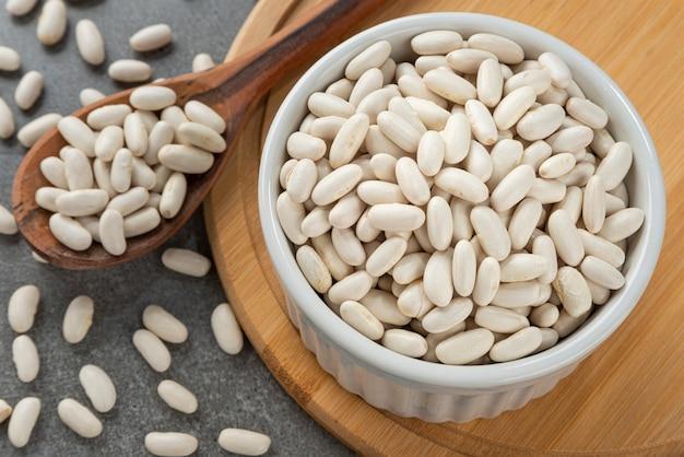 白豆の粒が入ったボウル木のスプーンと竹のサポートの詳細