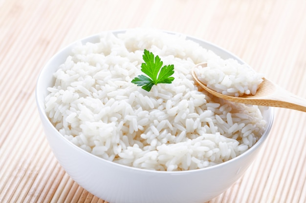 Bowl with white boiled rice with green fresh parsley for delicious healthy lunch. cereal food and dishes.
