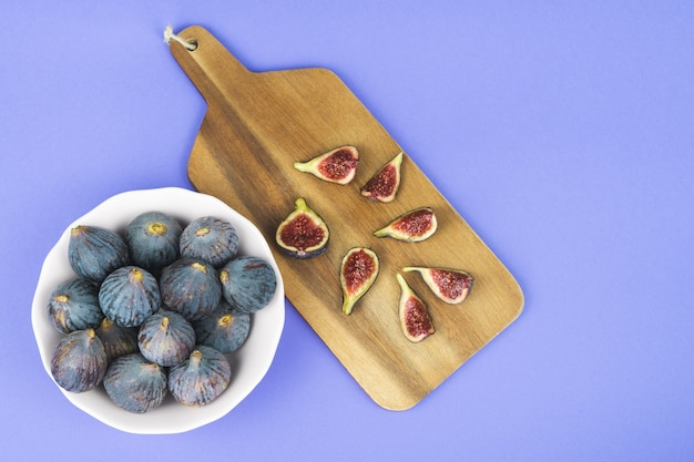 Bowl with whole figs, cut figs on kitchen table