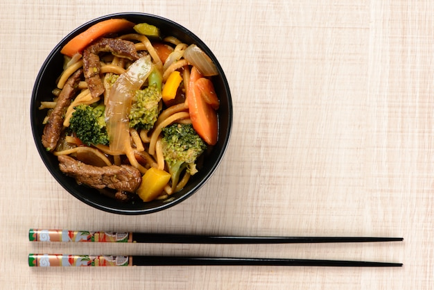 Bowl with yakisoba and hashi
