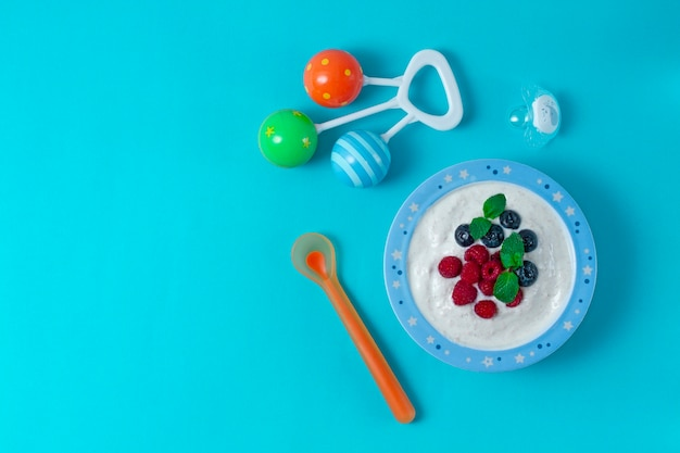 Bowl with yogurt, for a child, with blueberries and raspberries