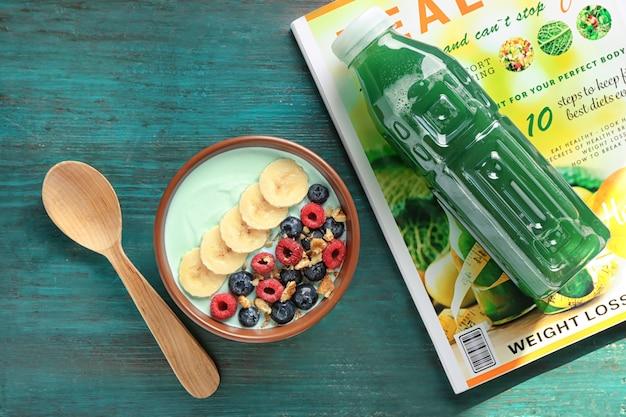 맛있는 스피루리나 스무디와 나무 테이블에 음료 한 병 그릇. 건강한 채식 음식 개념