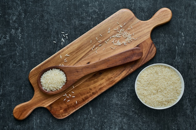 Bowl and wooden spoon with uncooked basmatti rice wooden cutting board