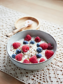Bowl of yogurt and berries with seeds on a crochet tablecloth placemat