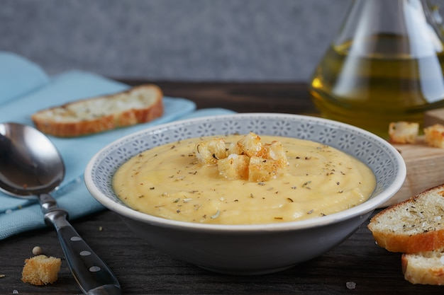 Bowl of zucchini and cauliflower cream soup on wooden table