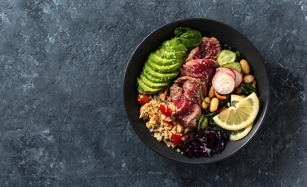 ビーフステーキ、豆、クスクス、アボカドと野菜の健康食品仏bowl