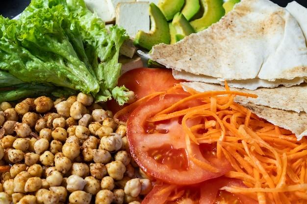 素朴なテーブルの上の仏bowlのクローズアップビュー。ひよこ豆、サラダ、野菜、豆腐、ピタパン、アボカドの完全菜食