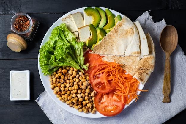 素朴なテーブルの上の仏bowlの平面図です。ひよこ豆、サラダ、野菜、豆腐、ピタパンとアボカドのビーガン料理、平干し