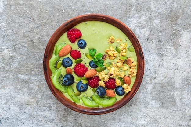 フルーツ、ベリー、グラノーラ、ナッツ、種子が入った緑のスムージー抹茶茶bowl。健康的なビーガン朝食