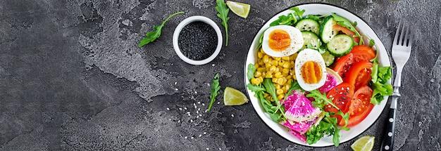 新鮮なサラダ。キュウリ、トマト、スイカ大根、レタス、ルッコラ、トウモロコシ、ゆで卵-新鮮な生野菜とボウルします。健康食品。ベジタリアン仏bowl。上面図。平置き