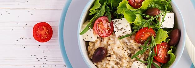 ビーガンサラダオートミール、トマト、チーズ、レタス、オリーブの朝食ボウル。健康食品。ベジタリアン仏bowl。バナー。上面図