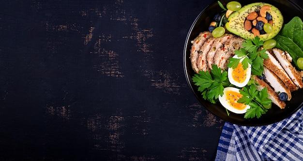 ケトジェニックダイエット。ミートローフ、鶏肉、アボカド、ベリー、ナッツ入りの仏bowl料理。デトックスと健康概念。ケト食品。オーバーヘッド、上面図、平置き
