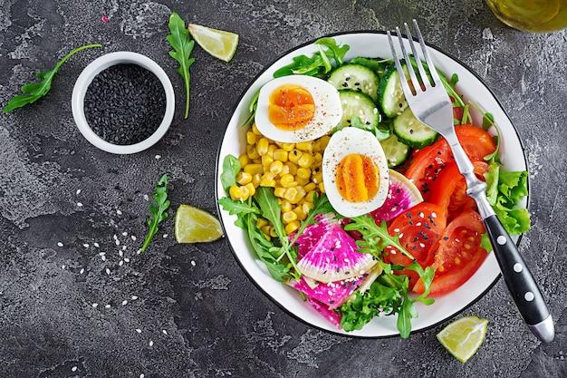 ベジタリアン仏bowl。キュウリ、トマト、スイカ大根、レタス、ルッコラ、トウモロコシ、ゆで卵-新鮮な生野菜のボウル。新鮮なサラダ。