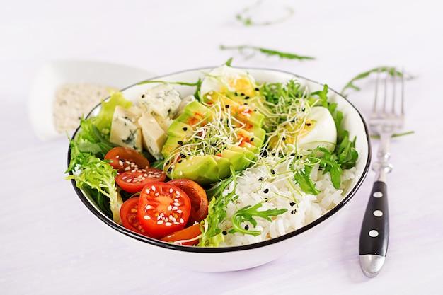 テーブルの上の卵、米、トマト、アボカド、ブルーチーズとベジタリアンの仏bowlボウルランチ。