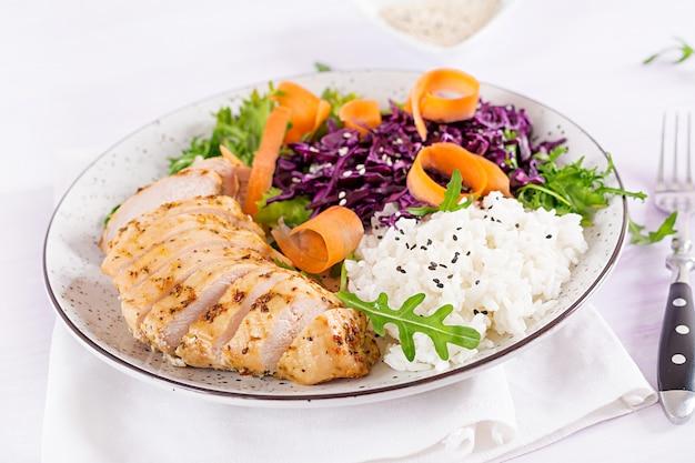 鶏の切り身、ご飯、赤キャベツ、ニンジン、新鮮なレタスのサラダ、ゴマを添えた仏bowl料理。