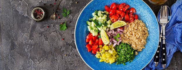 キノア、ルッコラ、ピーマン、トマト、キュウリの暗い背景上のボウルのサラダ。健康食品、ダイエット、デトックス、ベジタリアンのコンセプト。仏bowl。上面図。バナー。平置き
