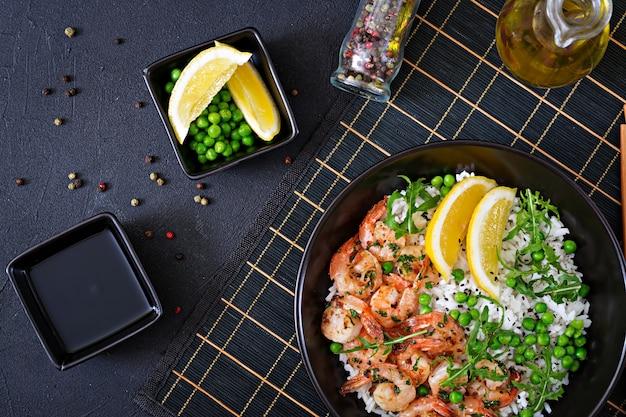 黒いボウルに若いグリーンピース、エビ、ルッコラとご飯。健康食品。仏bowl。上面図。平置き