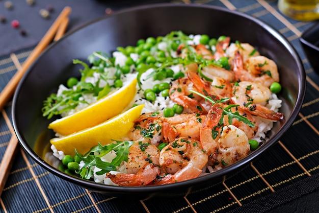 黒いボウルに若いグリーンピース、エビ、ルッコラとご飯。健康食品。仏bowl