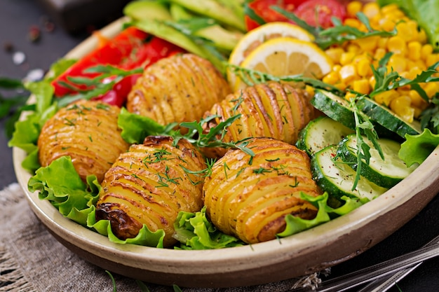 ベジタリアン仏bowl。生野菜とボウルに焼きたてのジャガイモ。ビーガンミール。健康とデトックス食品のコンセプト。