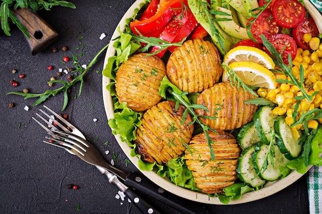 ベジタリアン仏bowl。生野菜とボウルに焼きたてのジャガイモ。ビーガンミール。健康とデトックス食品のコンセプト。上面図。平置き