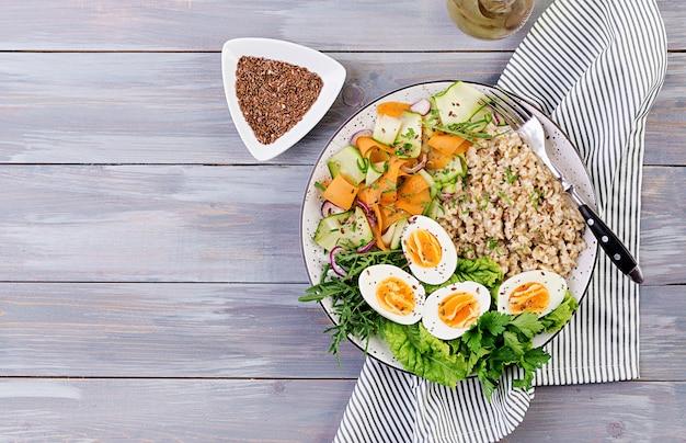 オートミール、ズッキーニ、レタス、ニンジン、ゆで卵の朝食ボウル。新鮮なサラダ。健康食品。ベジタリアン仏bowl。