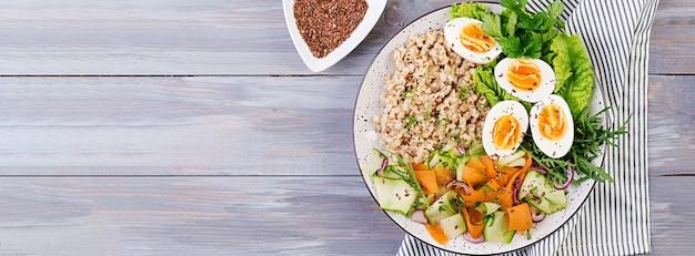 オートミール、ズッキーニ、レタス、ニンジン、ゆで卵の朝食ボウル。新鮮なサラダ。健康食品。ベジタリアン仏bowl。バナー。