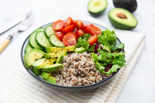 健康食品。キノア、アボカド、キュウリ、サラダ、トマト、オリーブオイルの仏bowl。