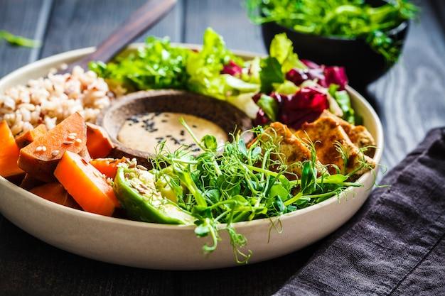 豆腐、アボカド、ご飯、苗、サツマイモ、タヒニドレッシングの仏bowl。