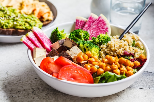 キノア、揚げヒヨコマメ、スモーク豆腐、白い皿に野菜の仏bowl